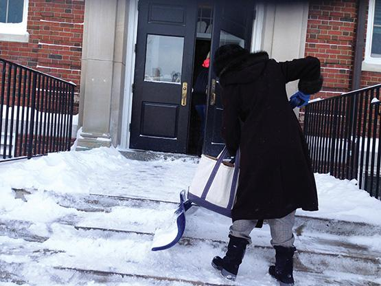 A faculty member shovels snow off the stoop outside Ketchem Hall.