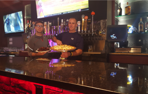 Michael Rizzo Jr. (left) stands with owner Michael Rizzo (right) holding their featured barbeque wings