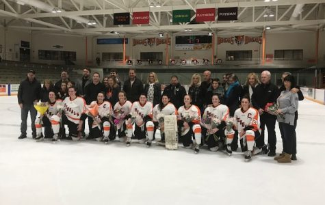 The senior women's hockey players line up for photos with their families after the Senior Day game.