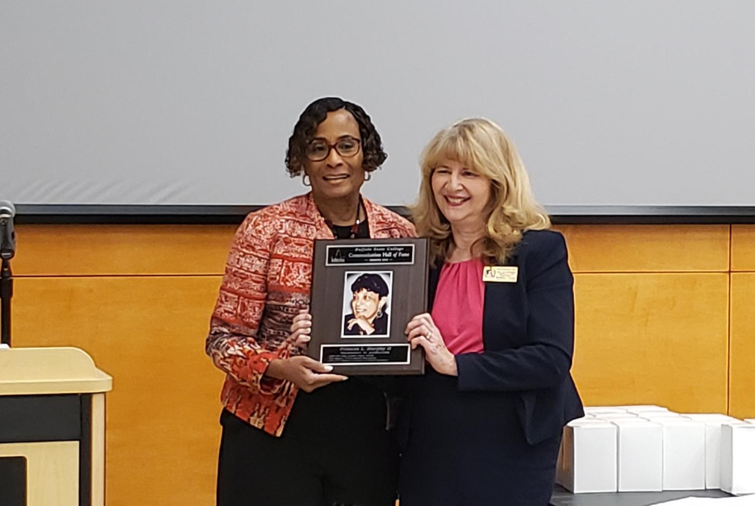 Dr. Toni Draper, daughter of Frances L. Murphy, accepts her mother's posthumous the induction into the Communcation Deaprtment Hall of Fame from chair Dr. Deborah A. Silverman.